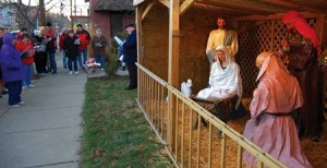 A group from local churches stands before a life size nativity scene singing Christmas carols.